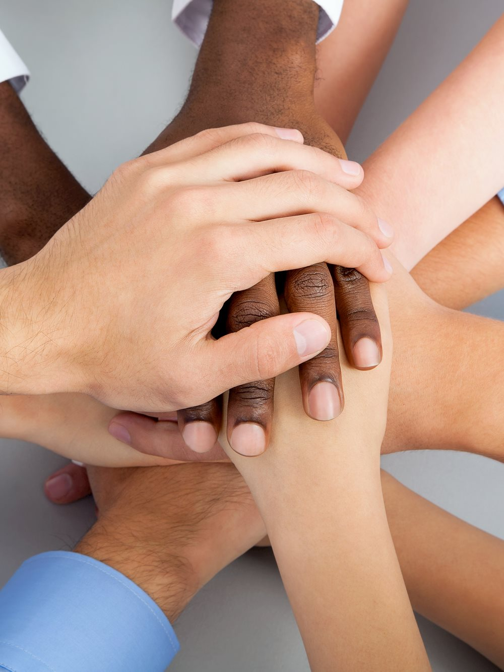 International Business Team Showing Unity With Their Hands Together.jpg